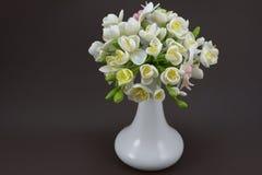 Handgemachter Polymerlehmblumenstrauß in einem weißen Vase auf einem dunklen backgro Stockfotografie