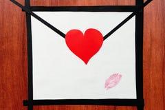 Handgemachter Umschlag mit Herz- und Lippenstiftkuß auf dem hölzernen ta Lizenzfreie Stockfotografie