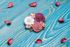Handgemachtes Bestehen der Brosche von den weißen, rosa und lila Blumen, die vom Stoff auf dem blauen Hintergrund machen lizenzfreie stockfotos