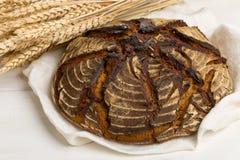 Handgemachtes Brotlaib mit den Weizenähren auf weißem Holz Stockbild
