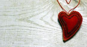 Handgemachtes Filzherz verziert mit Perlen auf hölzernem Hintergrund Stockbild
