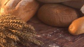 Handgemachtes geschmackvolles Brot, das auf Leinwand auf dem Holztisch mit Mehl, Weizen und den Ohren des Weizens liegt stock video footage