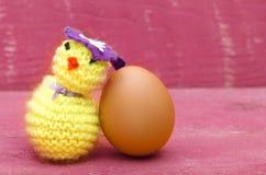 Handgemachtes gestricktes woolen Ostern-Huhn mit wirklichem Ei auf Rosa flehen an Lizenzfreie Stockbilder