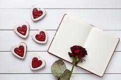 Handgemachtes Herz formte Plätzchen mit leerem Notizbuch und rosafarbener Blume auf weißem hölzernem Hintergrund für Valentinsgru Stockfotos