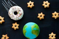 handgemachtes Modell des Erdplaneten, des Donutmeteorits und der Plätzchen in Form der Sterne auf der Tafel, Raum und lizenzfreie stockbilder
