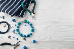 Handgemachtes T?rkisarmband, obenliegende flache gelegte Zusammensetzung mit Zange, Perlen und Werkzeuge stockfotos