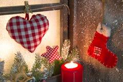 Handgemachtes Weihnachtshölzerne Fensterdekoration mit Herzen und einem roten Sankt-Stiefel Stockfotos