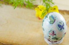 Handgemaltes Osterei mit kleinen Hühnern im Hintergrund Stockbilder