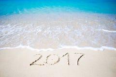2017 handgeschrieben auf sandigem Strand mit weichem Meereswogen auf Hintergrund Stockbild