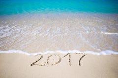 2017 handgeschrieben auf sandigem Strand mit weichem Meereswogen auf Hintergrund Lizenzfreies Stockfoto
