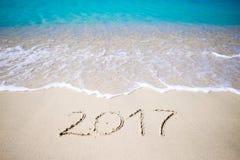 2017 handgeschrieben auf sandigem Strand mit weichem Meereswogen auf Hintergrund Stockfoto