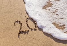 Handgeschriebene Aufschrift 20 auf dem Sand mit schäumender Welle Lizenzfreies Stockbild