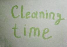 Handgeschriebene Reinigungszeit auf staubiger Oberfläche Stockbild