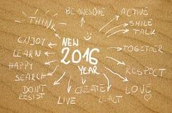 Handgeschriebene Wörter 2016 der Entschließungsidee auf einem wirklichen Hintergrund mit gelbem Sand Stockbild