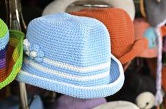 Handgestrickte Hüte am Schaufenster stockbild