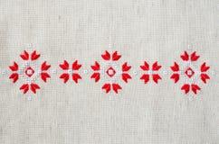 Handgjord broderi för beståndsdel på lin vid röda och vita bomullstrådar Bakgrund med broderi Arkivbild