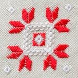 Handgjord broderi för beståndsdel på linne vid röda och vita bomullstrådar Bakgrund med broderi Arkivfoto