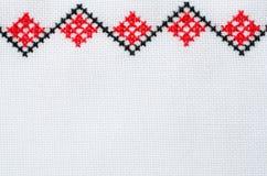 Handgjord broderi för beståndsdel på vit linne vid röda och svarta bomullstrådar arkivbild