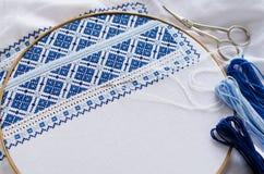 Handgjord broderi vid vit- och blåtttrådar Arkivbild