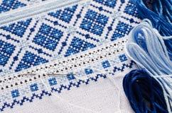 Handgjord broderi vid vit- och blåtttrådar Royaltyfria Bilder