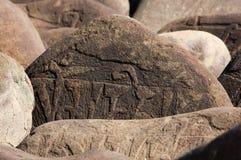 Handgjord buddistisk mantra på stenar Fotografering för Bildbyråer