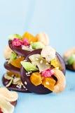 Handgjord choklad med kanderad frukt och muttrar Arkivbilder
