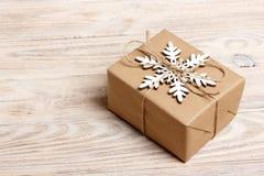Handgjord gåvaask för jul som dekoreras med den pappers- och vita snöflingan för hantverk på bästa sikt för vit träbakgrund Vinte Royaltyfri Fotografi
