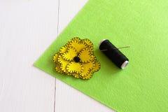 Handgjord gul sats för filtblommasömnad på den gröna filten och den vita träbakgrunden Royaltyfria Foton