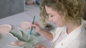 Handgjord lergods, den skickliga konstnärkvinnlign gör målning på clayware med borsten på seminariet arkivfilmer