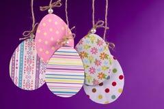 Handgjord påskbakgrund Grupp av kulöra ägg som göras av pappers- hängning på ett rep på en purpurfärgad bakgrund royaltyfri bild