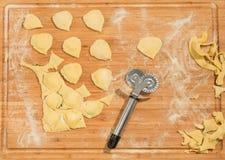 Handgjord ravioli och rå deg som täckas med mjöl Hjuldegskärare som förläggas på trätabellen Royaltyfri Bild