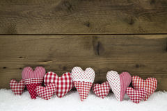 Handgjord röd vit kontrollerade hjärtor på en träjulbackgrou Arkivbilder