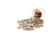 Handgjord träkorg och bunt av myntet som isoleras på vit Royaltyfri Foto