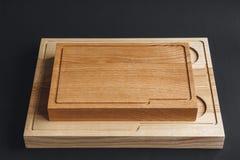 Handgjord träskärbräda för valnöt på svart träbräde royaltyfri fotografi