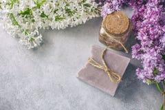 Handgjord tvål, den Glass kruset med doftande olja och lilan blommar för brunnsort och aromatherapy Arkivbilder