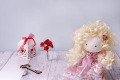 Handgjord tygdockaflicka på en vit trätabellcopyspace med den felika nyckel- pappers- rosen och gåvaasken arkivbilder