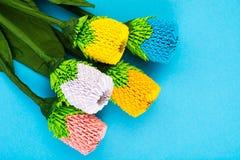 Handgjorda blommor för origami på blå bakgrund Arkivfoto