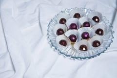 Handgjorda choklader ligger på den vita textilbakgrundstabellen Handgjorda sötsaker Arkivfoto