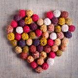 Handgjorda chokladgodisar som bildar hjärta, säckväv, kanfasbakgrund Fritt avstånd för din text royaltyfria foton