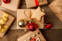 Handgjorda gåvaaskar för jul som dekoreras med hantverkpapper och den röda guld- handgjord kakastjärnan för bollar och på tappnin royaltyfri foto