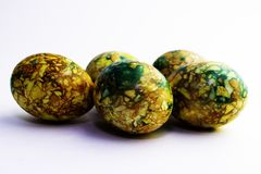 Handgjorda gula gr?na easter ?gg som m?las som marmoreras ?ver vit bakgrund royaltyfri fotografi