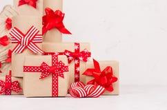 Handgjorda julgåvaaskar av kraft papper, julträdet med festliga röda band och pilbågecloseupen på vit träbakgrund arkivfoton
