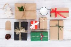 Handgjorda närvarande gåvaaskar för jul och lantlig garnering på det vita träbrädet royaltyfri foto