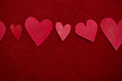 Handgjorda röda hjärtor på röd bakgrund Royaltyfria Bilder
