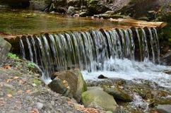Handgjorda trävattenavrinningar från små behandlade strålar Ett härligt fragment av en liten vattenfall Royaltyfri Foto