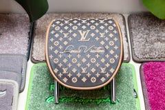 Handgjort brun och beigalädernackstöd Louis Vuitton för en bil i ett seminarium för medelinredesign mot bakgrunden av arkivbilder