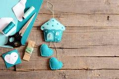 Handgjort filthus med hjärtor prydnad, hjälpmedel och material för hantverk för handdanandefilt, pappers- mallar på träbakgrund fotografering för bildbyråer