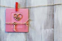 handgjort Stiliserad hjärta och tangent på jutekabel på rosa pappers- bakgrund Ljus naturlig träbakgrund arkivfoto
