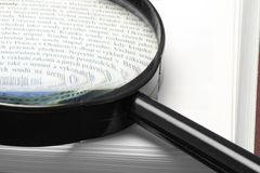 Handglass on a book. Magnifying glass on a book - close-up Royalty Free Stock Photo
