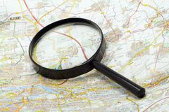 Handglass on a map. Magnifying glass on a map - close-up Stock Photography
